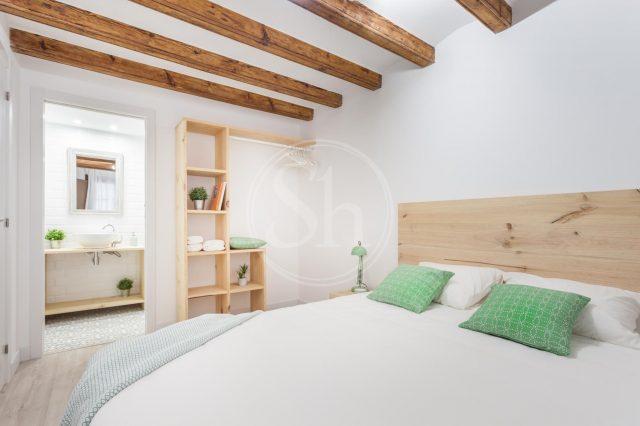 ein Schlafzimmer mit einem weiß bezogenem Bett, zwei grüne Kissen darauf und an der Wand steht ein Holzregal