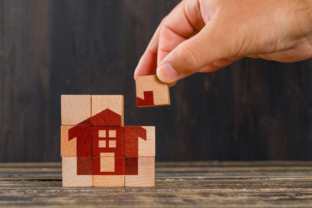 neun quadratische Holzklötze die richtig zusammen gestellt sind und somit ein rotes Haus zu sehen ist