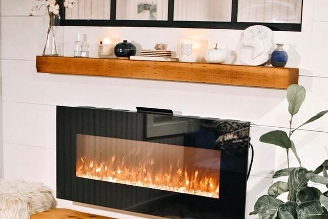 ein geschlossener Gaskamin, drum herum weiße Wand und darüber ein Holzregal mit weißen Dekorationselementen