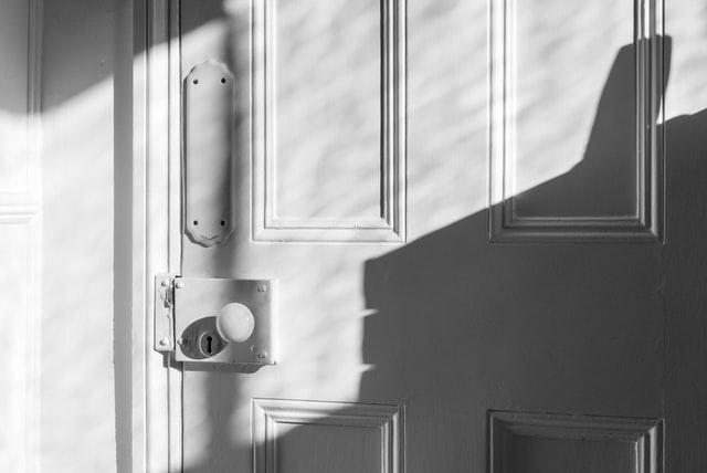 eine komplett weiße geschlossenen Tür mit runder Türklinke