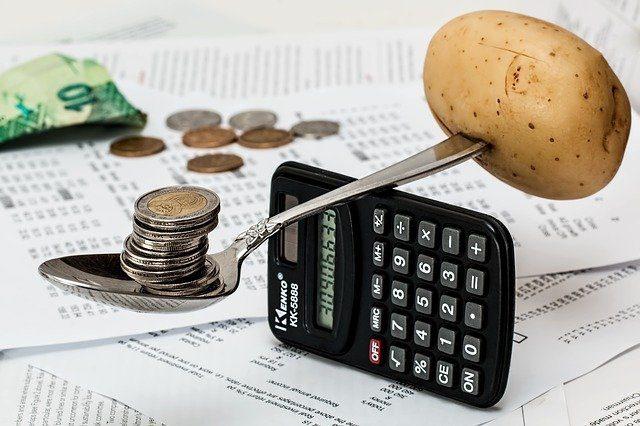 auf mehreren Dokumenten liegen vereinzelt Münzen und ein schwarzer Taschenrechner steht hochkant worauf ein Löffel an einem Ende eine Kartoffel und am anderen Münzen balanciert