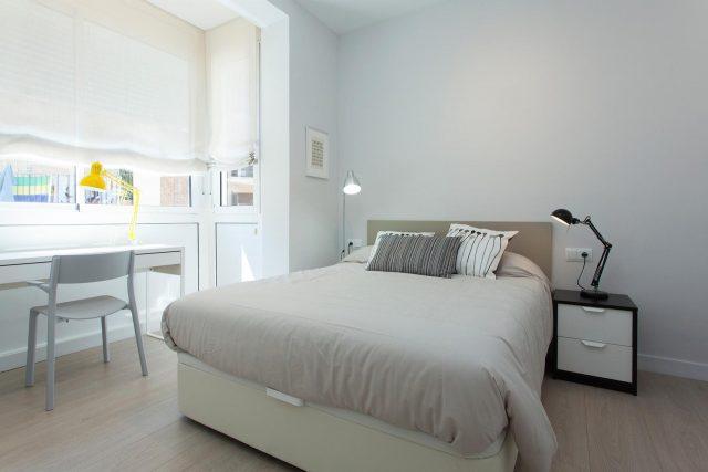 ein Schlafzimmer mit einem grau bezogenem Bett, links davon ein großes Fenster vor dem ein schreibtisch mit einer gelben Stehlampe steht