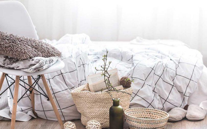 vor einem Bett mit karrierter Bettwäsche steht ein Holzhocker mit einem Kissen und einer Decke und am Boden zwei Weidenkörbe und eine grüne Flasche mit einem Zweig