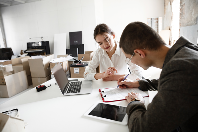 an einem weißen Schreibtisch sitzten eine Frau in weißer Bluse und ein Mann der etwas auf ein Papier schreibt, davor steht ein Laptop und dahinter sind Umzugskartons zu sehen