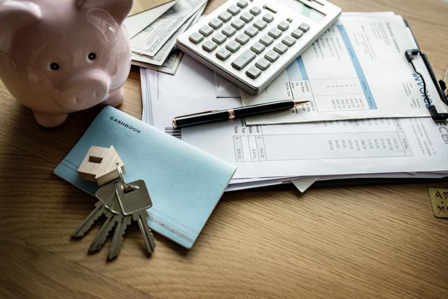 ein Holztisch auf dem ein rosanes Sparschwein steht und unter einem silbernem Taschenrechner mehrere Rechnungen, daneben ein kleines blaues Sparbuch mit einem Schlelbund und einem kleinen Holzhaus als Schlüsselanhängerü