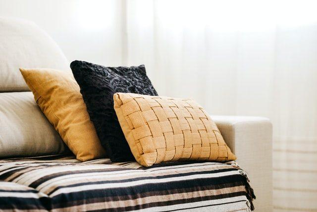 ein beiges Sofa mit einer Streifendecke und drei Kissen in schwarz und ocer Tönen