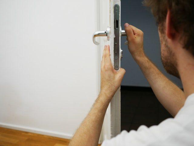 ein Mann der die Türklinke einer weißen Eingangstür überprüft