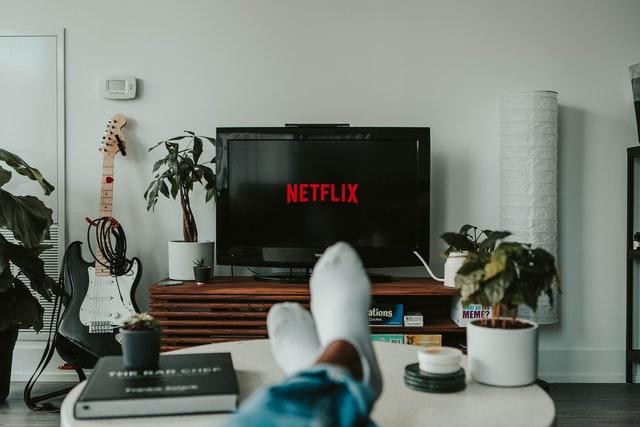 in einem Wohnzimmer sieht mand die Füße mit weißen Socken einer Person und dahinter ein Ferseher auf dem das Netflixlogo aufleuchtet
