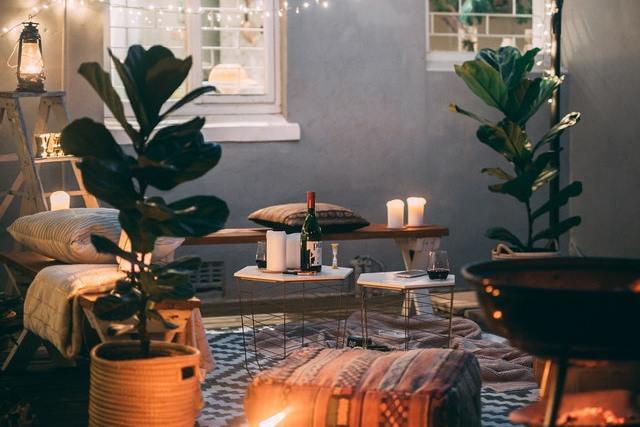 eine Terrasse mit einem weiß-schwarzen Teppich, zwei große Pflanzen, eine Holzbank mit Kissen, viele Kerzen und eine Lichterkette vor dem Fenster