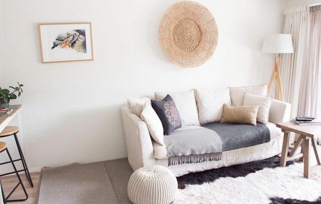 ein Wohnzimmer mit weißem Sofa auf dem eine graue Decke ausliegt, darauf steh ein dunkelgraues Kissen mit einem hellrotem Mandala darauf, dahinter eine Stehlampe, davor ein Kuhfellteppich und ein weißer gehäckelter Puff