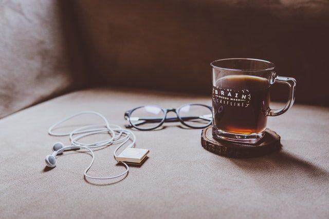 ein Glas mit Schwarztee auf einem Holzunterstzer, links daneben eine blaue Brille und links davon weiße Kopfhörer mit einem MP3-Player
