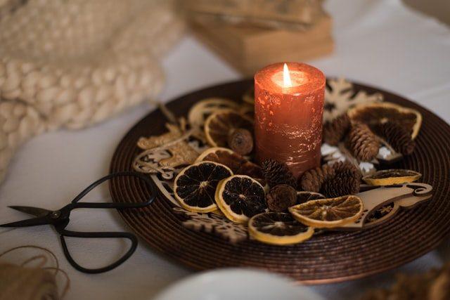auf einer weißen Tischdecke steht ein bronzefarbener Teller in dem in der Mitte eine angezündete orangene Kerze steht und rund herum getrocknere Orangenscheiben und kleine Tannenzapfen