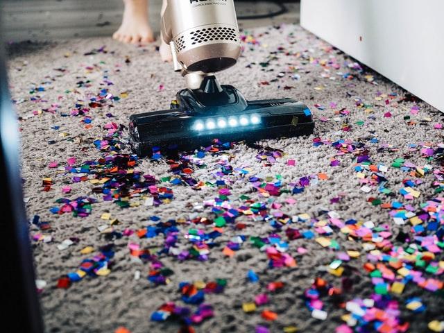 jemand der buntes Glitzerkonfetti von einem Teppich mit dem Staubsauger entfernt