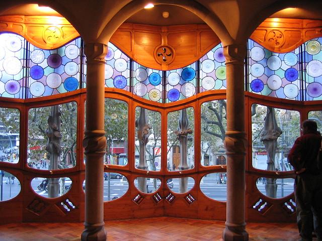 von innen zwei Säulen unter einer gewölbten Decke und dahinter die großen farbigen Fenster mit verschiedenen Formen