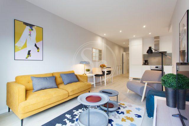 ein Wohnzimmer mit gelbem Sofa und grauen Kissen, davor zwei runde kleine grau Tische auf einem buntem Teppich und ein grauer und ein blauer Sessel gegenüber