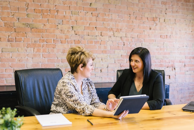 in einem Büro sitzen zwei Frauen nebeneinander, eine erklärt der anderen etwas auf einem Tablet