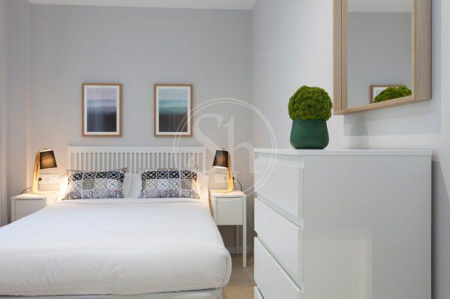 ein Schlafzimmer mit einem weißen Bett darüber hängen zwei Landschaftsbilder, rechts ein weißer Schrank mit einer grünen runden Pflanze darauf