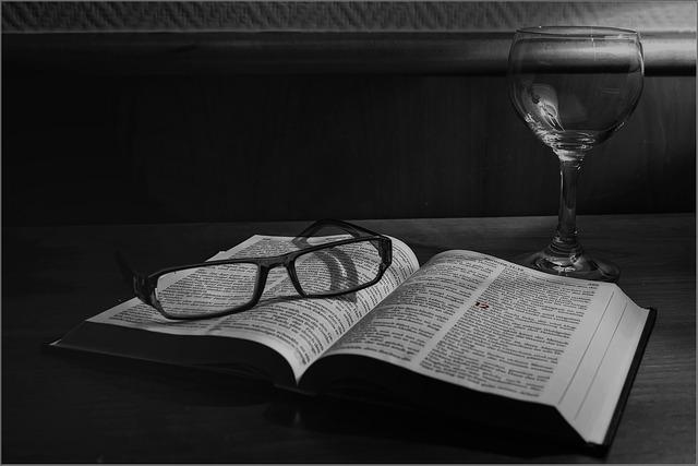 ein offenes Buch auf einem Holztisch mit einer Brille darauf und einem leeren Weinglas auf der rechten Seite