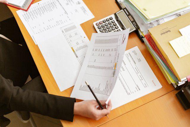 Eine Person die an einem Holzschreibtisch, auf dem viele Dokumente liegen, arbeitet