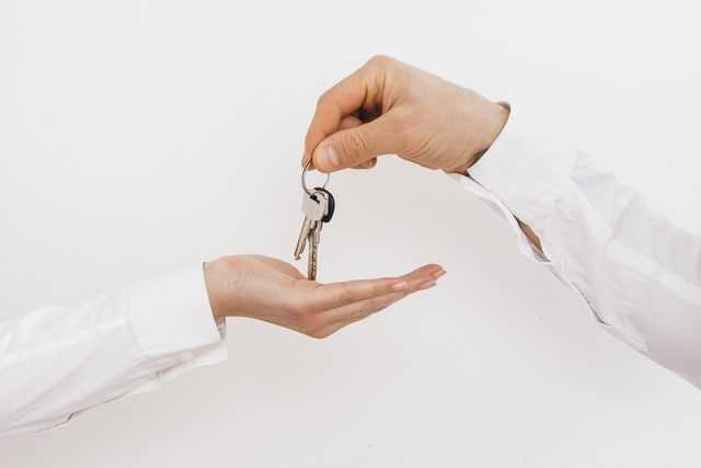 Ein weiblicher und ein mänlicher Arm, beide weiß gekleidet und eine hand gibt der anderen einen Hausschlüssel.