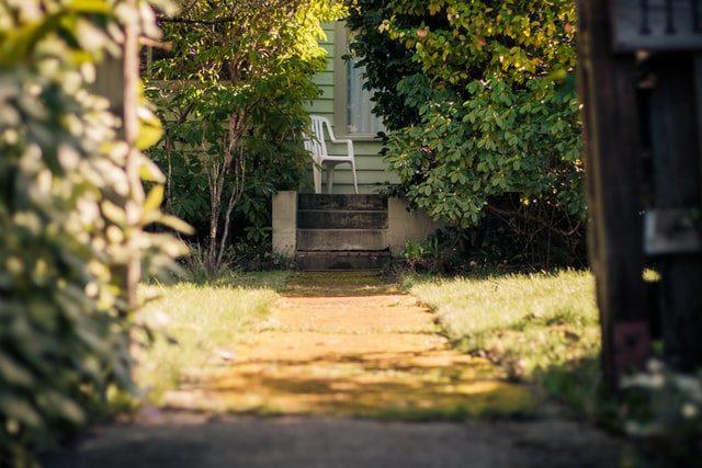 Der Garteneingang zu einem Haus, am Ende gibt es einige Treppen und oben auf der Terrasse steht ein weißer Plastikstuhl.