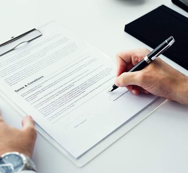 zwei Hände einer Person die gerade einen Vertrag mit einem schwarzem Kugelschreiber unterschreibt