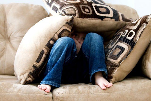ein Kind mit einer Jeanshose das unter Kissen begraben auf einem beigem Sofa sitzt