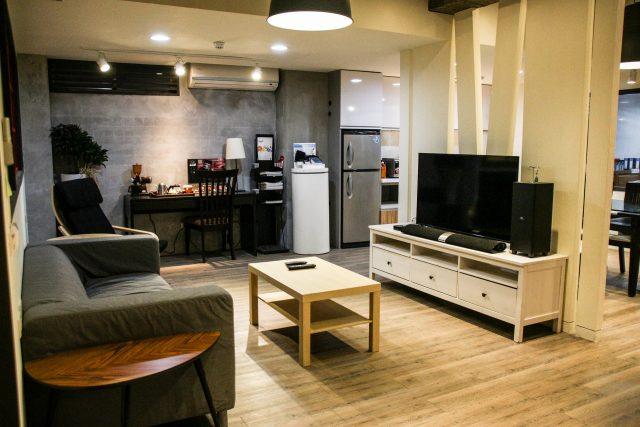 ein Wohnzimmer mit eine grauen Zweisitzersofa, davor ein kleiner rechteckiger Holztisch und an der anderen Wand ein weißer niedriger Schrank mit einem Fernseher darauf