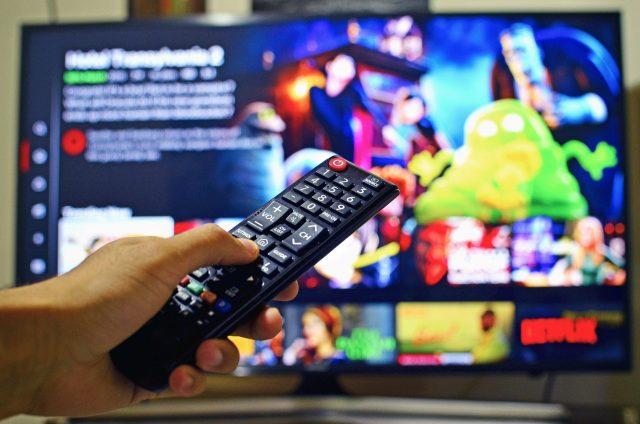 die linke Hand einer Person mit einer Fehrnbedienung, im Hintergurnd ein eingeschaltener Fernseher