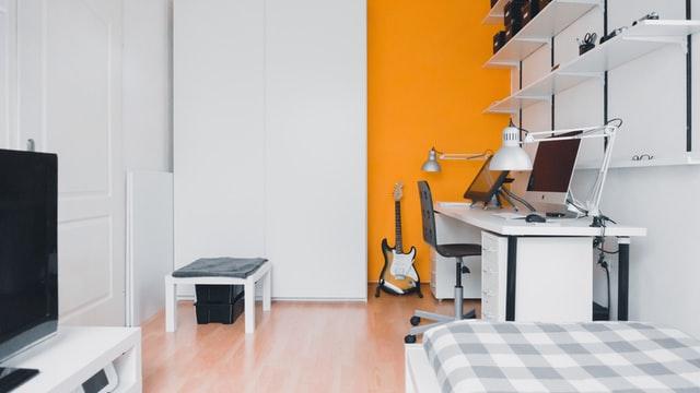 ein Zimmer mit einem Bett rechts, links ein Fernseher und vor dem Bett eine weißer Schreibtisch mit einem schwarzen Stuhl