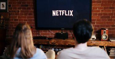 ein junges Pärchen das auf dem Sofa sitzt und Netflix in einem Fernseher an der Wand schaut