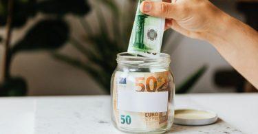 ein Glas in dem schon 50 Euro drin sind und eine Hand gerado weitere 100 Euro reinsteckt