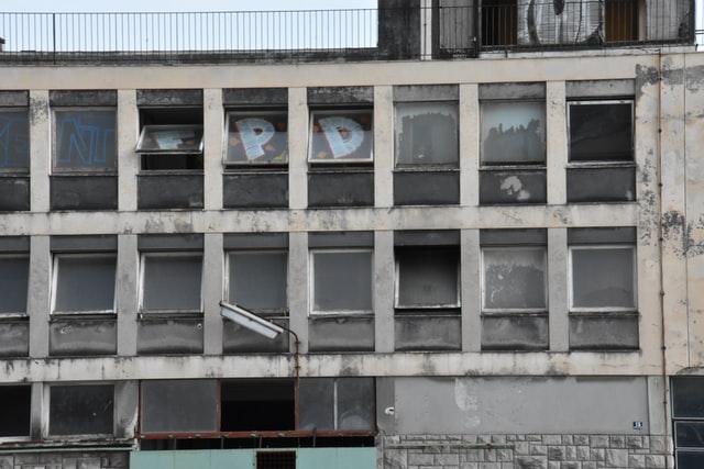 ein heruntergekommenes Gebäude von außen, einige Fenster sind kaputt und andere von Innen mit Grafiti besprüht