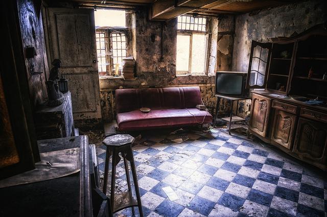 heruntergekommenes Wohnzimmer mit einem alten rotem Ledersofa, kaputter Fernseher und andere abgenutzte Holzmöbel