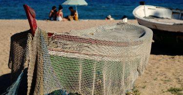 am Strande ein kleines Fischerboot, das mit einem Netz bedeckt ist, im Hintergrund siitzen drei Freunde im Sand unter einem Sonnenschirm und spielen Karten
