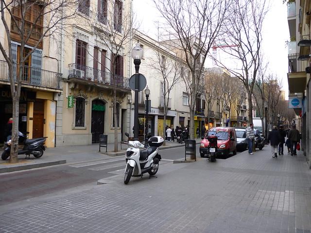 eine Straße im Bezirk Sant Andreu mit vielen Bäumen und geparkten Autos