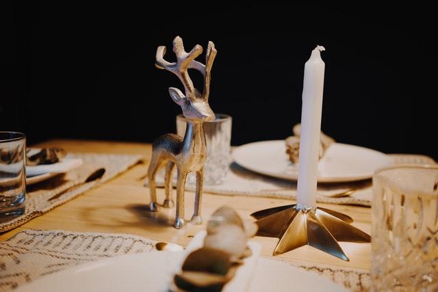 ein weihnachtlich gedeckter Holztisch mit einer weißen Kerze auf einem sternförmigen Kerzenständer und daneben eine silberne Rentierfigur