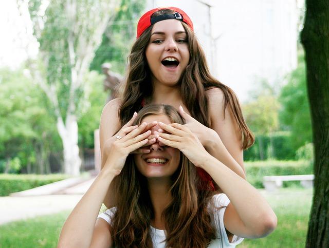 ein junges Mädchen mit einer roten Kappe und langen braunen Haaren die einem anderen Mädchen von hinten die Augen zuhält