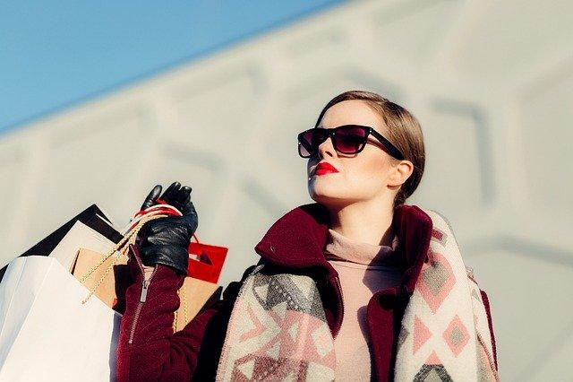 eine Frau in rotem Mantel mit schwarzen Handschuhen, Sonnenbrille und roten Lippen die in die Ferne schaut und mehrere Einkaufstüten über der Schulter trägt