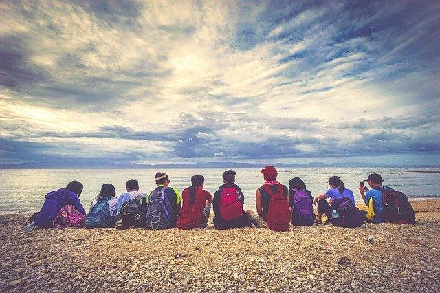eine Gruppe von Schülern die mit ihren Ruchsäcken im Halbkreis am Strand Richtung Meer sitzten