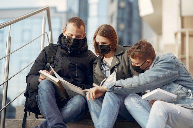 drei Studenten, zwei Männer und eine Frau in der Mitte, die alle schwarze Gesichtsmasken tragen, draußen auf einer Treppe sitzen und auf ein Buch schauen und zeigen