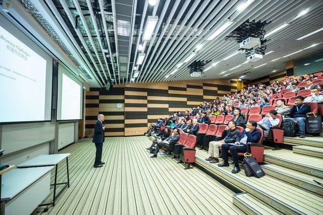 ein Vorlesungssaal in einer Universität mit roten stühlen und vielen Studenten die aufmerksam dem Profesor vorne zuhören