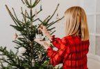 eine blonde Frau im kariertem rotem Hemd steht vor einem geschmücktem Weihnachtsbaum und hängt ein kleines weißes Häuschen dran