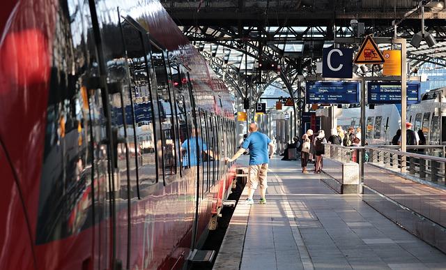 Bahnsteig an dem ein roter Zug gehalten hat und ein Man in blauem t-Shirt den Knopf drückt um die Tür zu öffnen