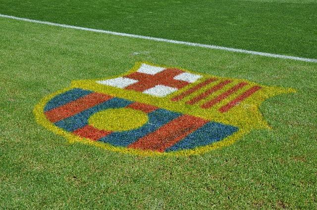 der grüne rasen des Stadions auf dem das Wappen des FCBarcelonas gemalt ist
