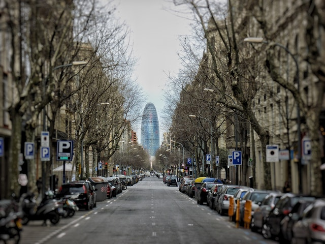 eine lange Straße Barcelonas mit geparkten Autos und Bäumen an beiden Straßenseiten und am Ende ist der Agbar Turm zu sehen