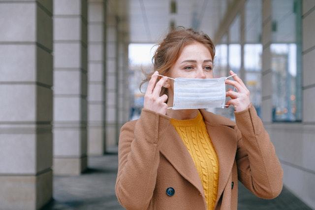 eine blonde Frau mit gelben Pullover und beigem Mantel die sich gerade eine OP-Maske aufsetzt
