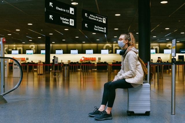 Eine junge Frau die in einem Flughafen auf ihrem kleinen weißen Koffer sitzt und wartet.