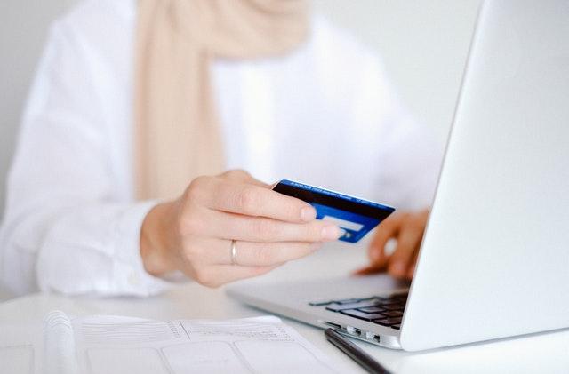 eine Frau mit weißer Bluse und rosanem Schal die vor einem silbernem Laptop sitzt und in ihrer rechten Hand eine blaue Kreditkarte hält