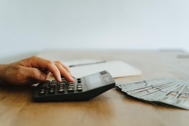 ein Holztisch auf dem eine Hand an einem Taschenrechner zu sehen ist und davor liegen mehrere Geldscheine und dahinter ein Notizbuch mit einem Kugelschreiber in der Mitte
